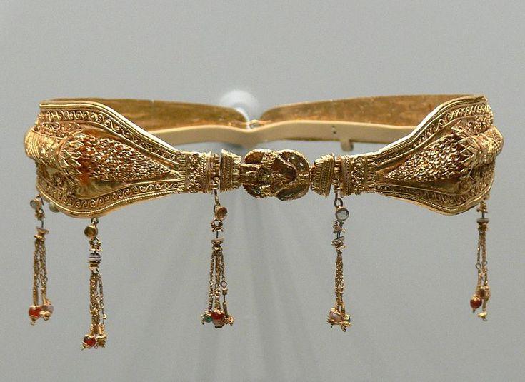 Diadema de oro con una representación del Nudo de Heracles en la parte central, y con motivos colgantes ornamentados con otros materiales, probablemente cristales de color azul, rojo y perlas. probablemente hecha en Alejandría, Egipto, 220 – 100 a.C. La pieza probablemente perteneció a una mujer noble de la dinastía Ptolemaica de Egipto.