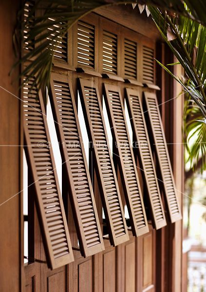 An exterior shot of French-style shutters at La Residence d'Angkor, Siem Reap, Cambodia. The resort's architecture is a fusion of French colonial and classic Khmer design.
