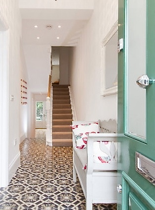Bright and light entrance hall with Spanish encaustic patterned tiled floor and stair runner.