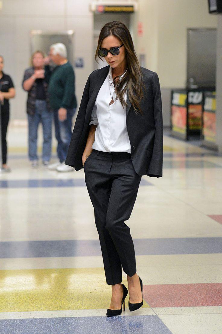 Victoria Beckham fotografiada llegando al aeropuerto JFK con un traje de color gris de estilo masculino, camisa blanca, salones negros de Manolo Blahnik y gafas de sol de Victoria Beckham Collection.