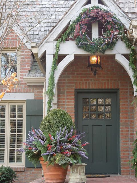 Love the color of the front door, shutters and potted boxwood with flowers.