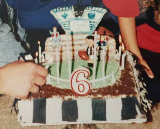 1990 Football Stadium/Oval -yes Collingwood!  Scoreboard made from rolled out icing left to dry decorate with royal icing. Green sprincles for oval. Grand stand made from cut cake showing melted chocolate layers. Chocolate sprinkles for ground and black food coloring painted onto marzipan banner.
