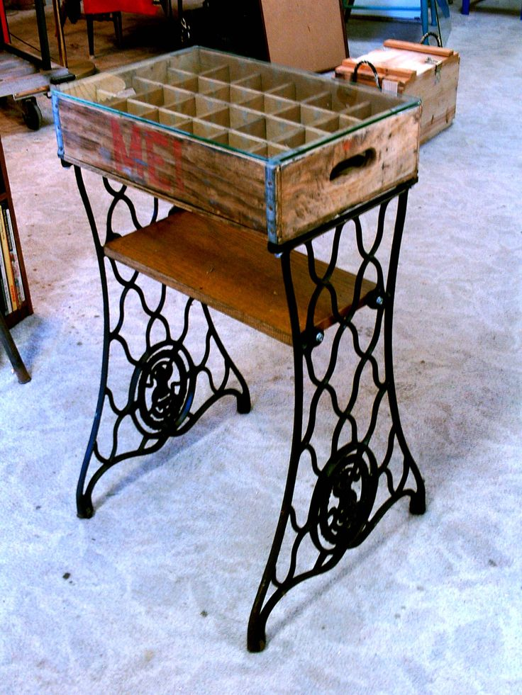 Singer sewing machine legs, a pop crate, glass and a board from an old bookshelf came together to make a really cool side table with display cubbies.