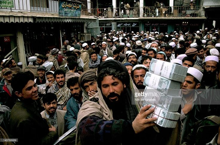 Stock Photo : 'Businessman' carries a bundle of notes. This currency exchange bazaar in Kabul will form the Afghan stock market, Afghanistan.