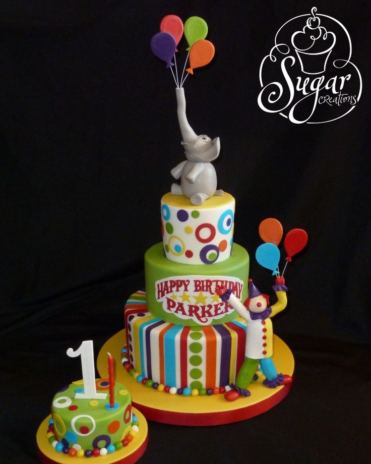 Circus theme first birthday! Rice Krispie treats and modeling chocolate inside the baby elephant and the clown -- the message plaque was hand-cut from a sheet of gumpaste
