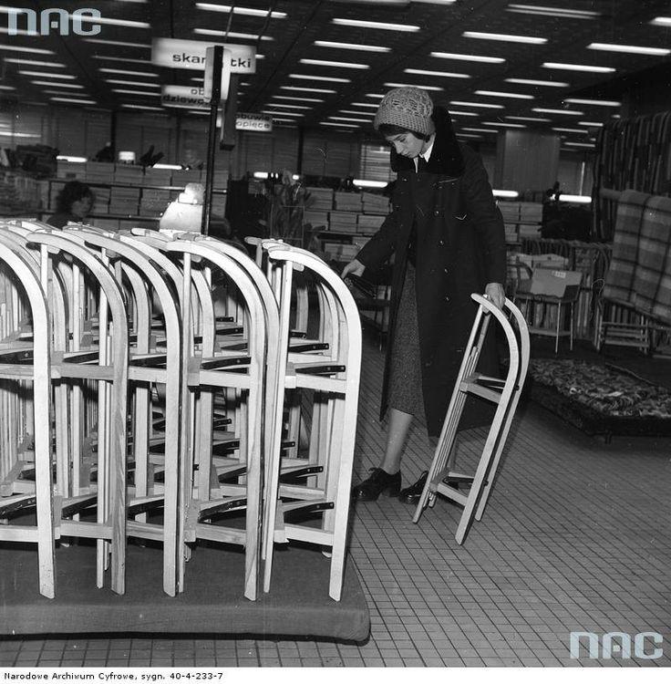 Fragment wnętrza sklepu. Na pierwszym planie kobieta ogląda sanki.