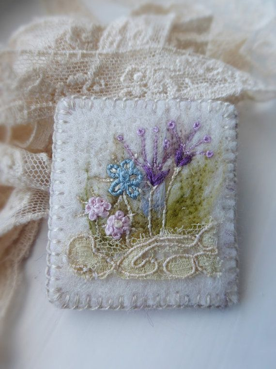 Embroidered Flowerbed Felt Brooch with Antique Lace  A small neat brooch embroidered on 3mm artisan felt, a dream to stitch on. First I needle felted a light background of mixed felt fibers. Then added tiny hand embroidered stitched flowers to make up this flowerbed in light shades of blue pink and lavender. A small piece of Edwardian lace at end adds a tough of history.  Wildly vintage little brooch, for lovers of stitch and lace !!!! Nice on a coat or jacket or pretty at top button of a…
