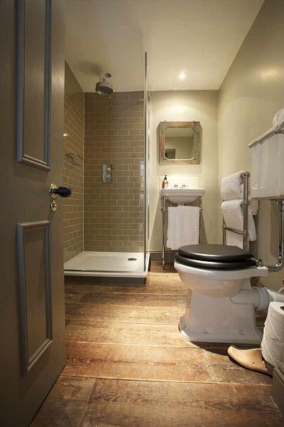 The Wheatsheaf Inn - bathrooms - corner shower, corner shower ideas, gray door, bathroom door, gray bathroom door, gray subway tiles, gray subway tile backsplash, rain shower head, wide plank floor, reclaimed mirror, reclaimed wood mirror, 2 leg washstand, towel warmer,