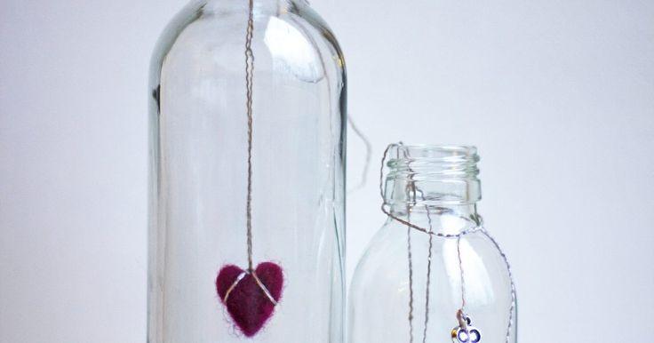 Cómo hacer decoraciones navideñas con botellas de vidrio. Las botellas de vidrio transparente con cuellos altos son grandes opciones a la hora de escoger elementos para realizar decoraciones navideñas. Su forma se asemeja a la de un árbol, por lo que no es difícil decorarlas como uno. Haz varios adornos con estas botellas, coloca luces navideñas en su interior y ubícalas en el marco de la ventana o en el ...