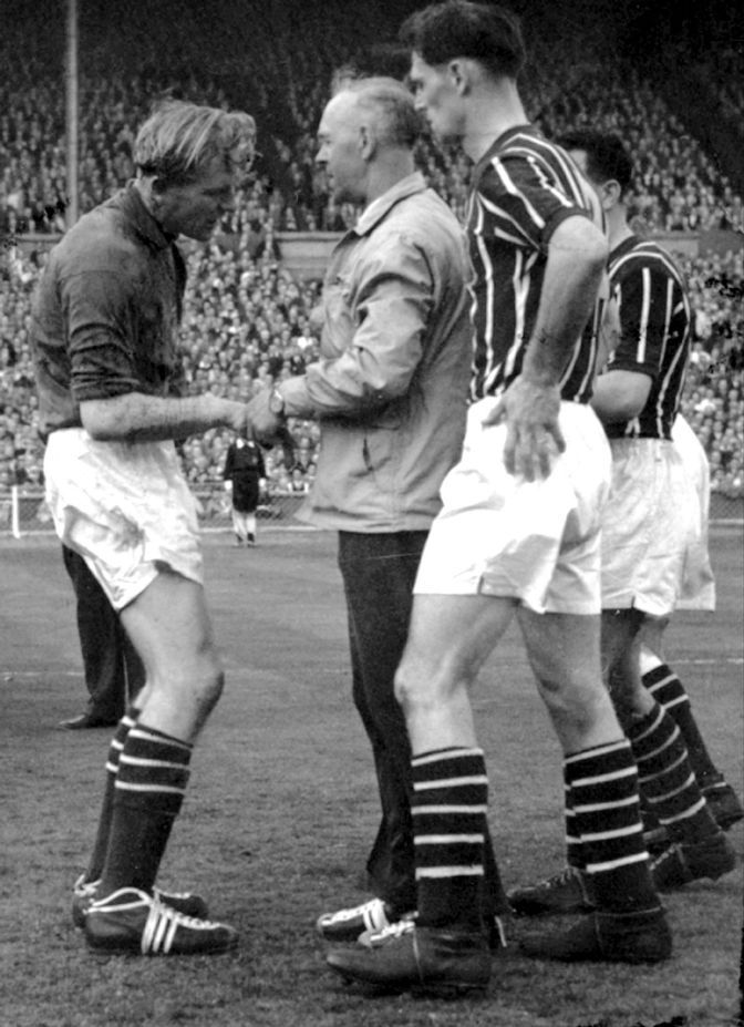 Bert Trautmann is treated by the City physio during the 1956 FA Cup Final against Birmingham City in which the City keeper played out the last 15 minutes with a broken neck.