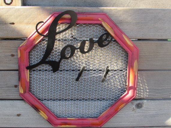 This red octagon wooden frame has chicken wire wrapped in the center with a metal wire and two black paper clips for hanging pictures, recipes, cards etc. A metal Love sign is attached to the top. Makes a great Valentines Day gift too! Measures- 13 1/2