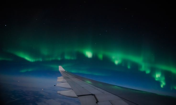 Aerial view of Northern Lights (Aurora Borealis) from an airplane flying over Northern hemisphere ©Shaarila / Shutterstock