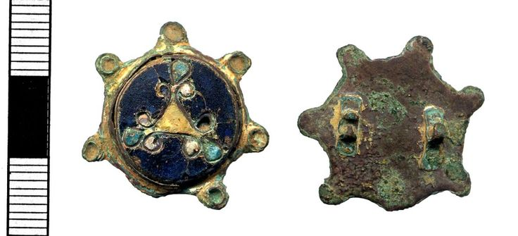 Copper alloy disc brooch with seven lobes, one of which is now missing, and cloisonné enamel centrepiece EARLY MEDIEVAL Circa AD 901 to: AD 1100