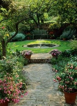 A simple sunken circular water feature with brick edging. In such an intimate setting you can get away with surrounding this with grass rather than more paving.