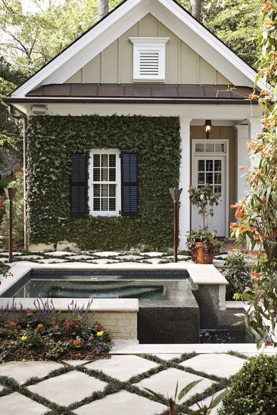 White, black, and green house exterior with ivy growing