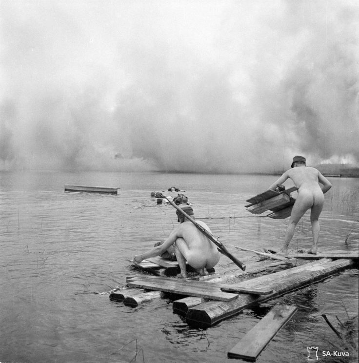 Finnish soldiers undergo training at Lake Khizhozero (in Finnish, Hiisjärvi) near Medvezhyegorsk in the Karelo-Finnish Soviet Socialist Republic (now the Republic of Karelia in Russia) during their conquest of East Karelia in the Continuation War (July 29, 1942). After assembling blocks of wood to ferry their weapons and clothing across the lake, they must swim through a smokescreen to the opposite bank. Photographed by Erkki Viitasalo.