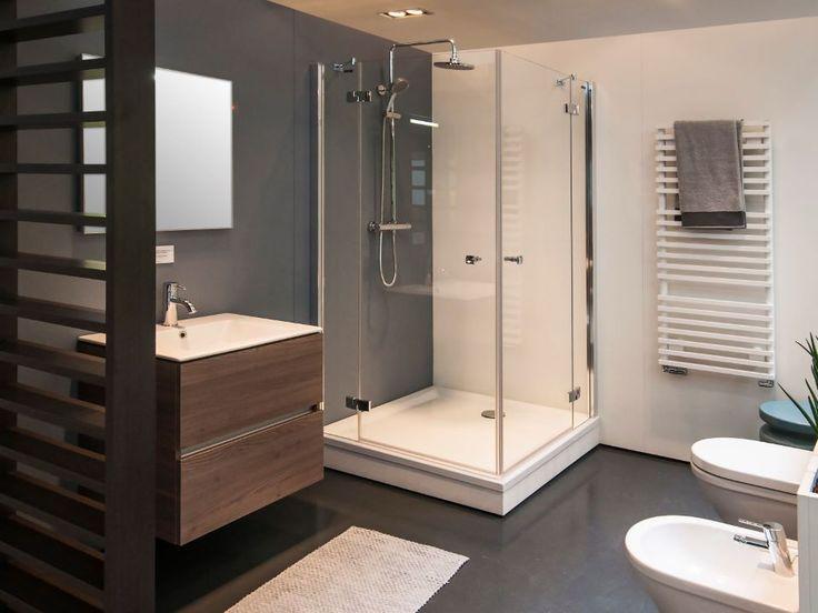 Een donkergrijze muur, natuurlijke houttinten en materialen en een ruime douche. Badkamer #inspiratie | Badkamermarkt.nl