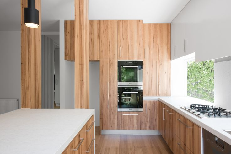 Straight-Laced house by windust architecture + design. Sunny kitchen with view to green wall.