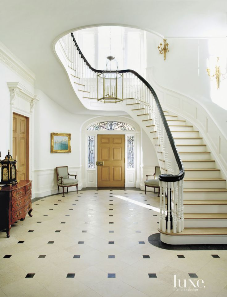 Traditional white entry with curved staircase luxe for Round staircase designs interior