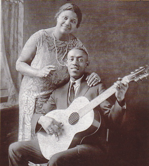 """Blues guitarist, Sylvester Weaver, and blues singer, Sara Martin. Their recordings are the very first country-blues recordings and the first known recorded songs using the slide guitar style. """"Guitar Rag"""" (played on a Guitjo) became a blues classic and was covered in the 1930s by Bob Wills and the Texas Playboys as """"Steel Guitar Rag"""" and became a country music standard too."""