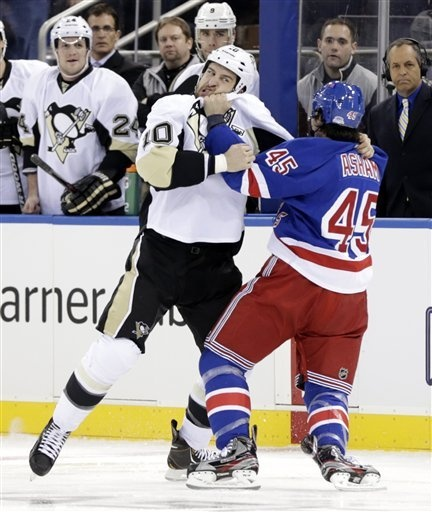 Pittsburgh Penguins' Tanner Glass, left, and New York Rangers' Arron Asham fight during the opening seconds of the first period of the NHL hockey game in New York, Sunday, Jan. 20, 2013. (AP Photo/Seth Wenig)