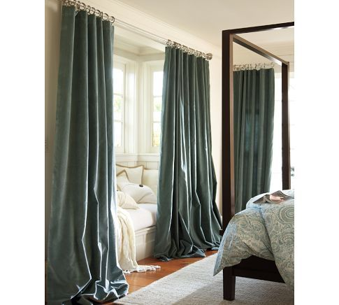 Rich blue velvet curtains block out light and add a luscious air of sophistication