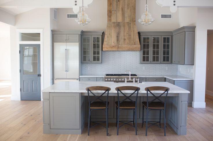 Grey farmhouse kitchen . open concept . custom barnwood hood . pantry door.  .