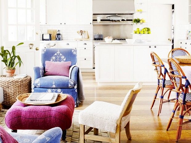 9 Things Every First-Time Homeowner Needs // A traditional open plan kitchen, dining, and living room with a blue armchair, purple ottoman, and French bistro chairs.