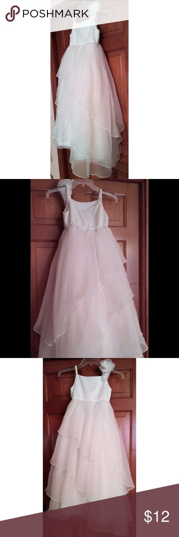 """David's Bridal Spaghetti-Strap Flower Girl Dress This satin and tulle flower girl dress features flower embellishments on one strap, and a voluminous, layered skirt.   The dress has a back zipper, and is fully lined.   Please note: There are 3 small holes located along the hem of the dress. One of the holes is shown in one of the pictures.   Color: soft white   The size is 6; approximate measurements: Length: 39"""" Bust: 11.5""""   The dress hangs slightly longer on one side.     Used; Good…"""