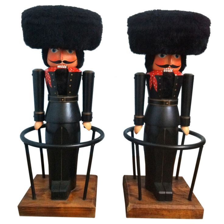 Pair of German Nutcracker Bar Stools  Germany  Mid 20th Century  Beautiful matching pair of German nutcracker barstools - Magnificent attention to detail in craftsmanship and painting. Back lever opens and closes the mouth, accented with a faux fur hat (seat). Sits on a wood base, iron footrest surrounds the each piece.
