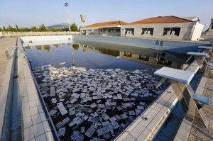 #athens Olympic Games 10 years later - Het zwembad in het Olympisch Dorp wordt al tijden niet meer gebruikt. Vuilnis drijft in het water.