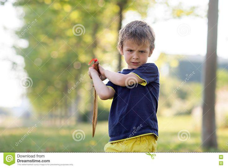 Niño Pequeño Enojado, Sosteniendo La Espada, Deslumbrándose Con Una Cara Enojada En Foto de archivo - Imagen: 70619470