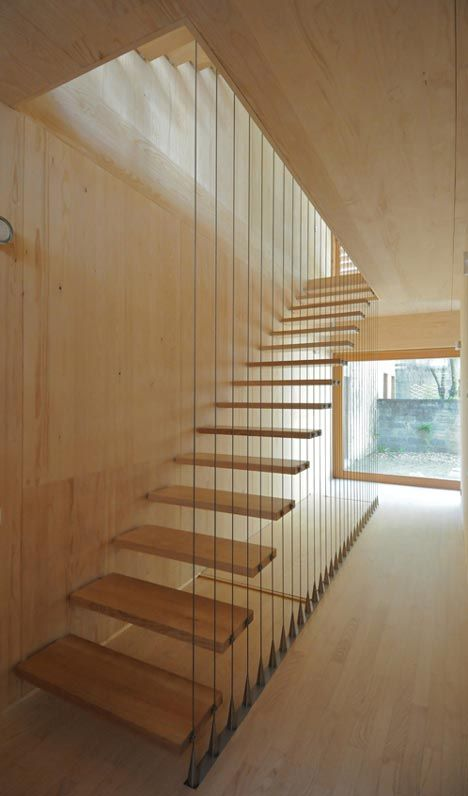 A staircase with cantilevered treads runs along the side of this French house