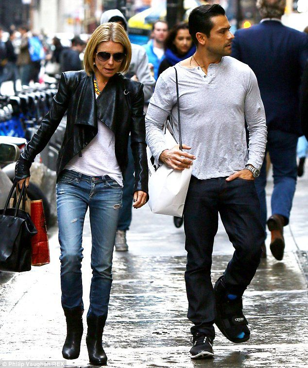 November rain: The TV personality walks around Soho in the wet weather with her husband Mark Consuelos, who sported a cast on his left foot
