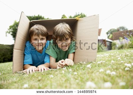 Portrait of two happy boys lying in cardboard box in the backyard - stock photo