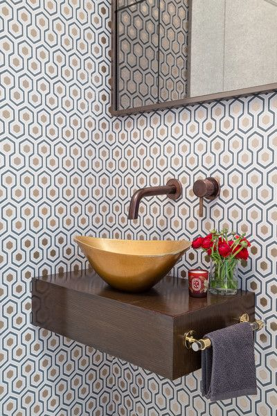 Tile bathroom with gold sink and red flowers next to it.