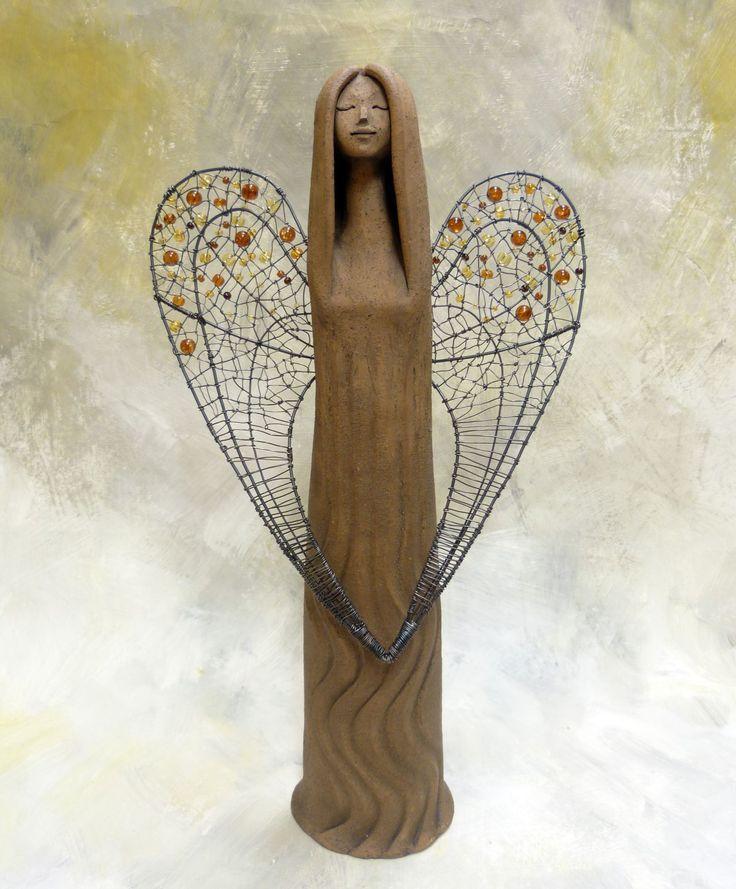 Devecia - anděl s drátovanými křídly Soška anděla je vyrobená z tmavé strukturní hlíny a je ozdobena drátovanými křídly srdčitého tvatu s vpletenými hnědožlutými korálky. Výška sošky je cca 40cm Rozpětí křídel je cca 22cm
