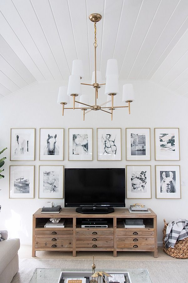 Great idea for decorating around your TV - hang similar sized art pieces in a grid around it! Sala paredes blancas mueble tv madera cuadros marcos dorados persianas beige y blanco seccional hueso