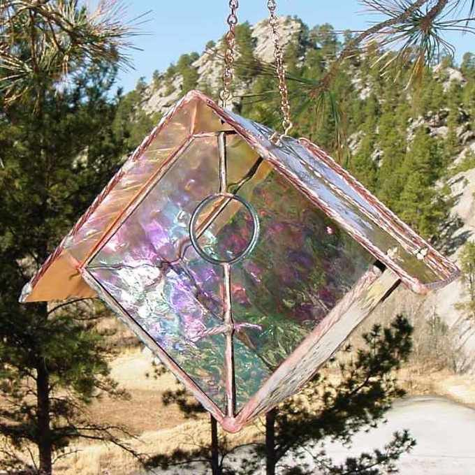 Stained glass hanging bird feeder is functional art for the garden. Hopper style feeder features a copper tray with ample perching space for several birds to feed at once. With hand hammered copper ro