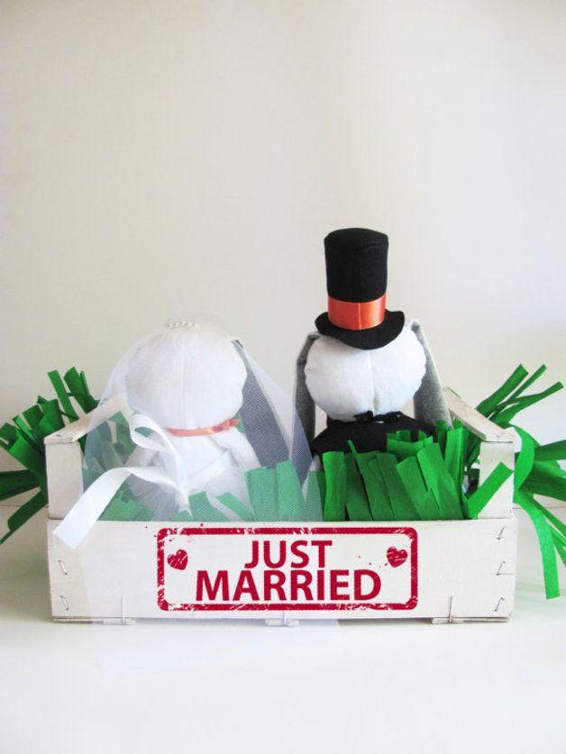 Congratulazioni alla nuova coppia!  Questa adorabile coppia di coniglietti è una perfetta idea regalo per una coppia di sposi, o una decorazione originale per la casa di sposi novelli.  Lo sposo indossa un gilet nero decorato con bottoni dorati, una tuba con nastro arancione, un papillon e una spilla-carota. La sposa indossa un velo di tulle decorato con perle, una gonna di tulle soffice e voluminosa, un nastrino al collo e un bouquet-carota.
