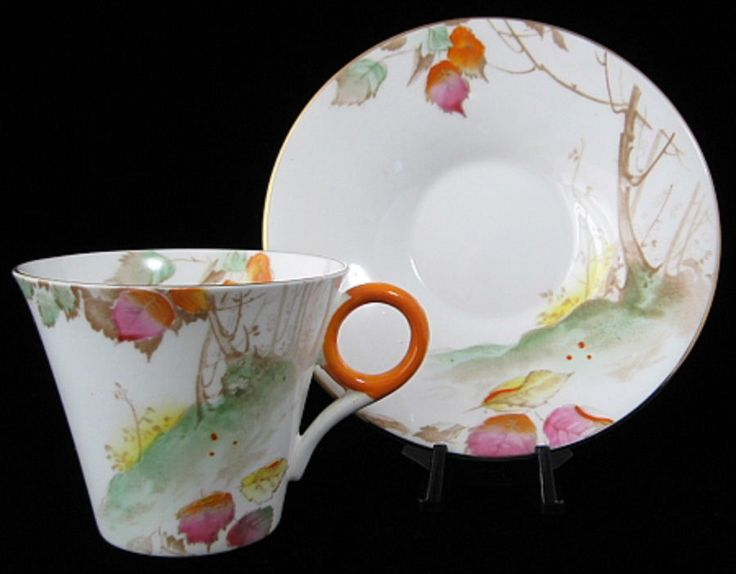 This is a Shelley China, England art deco design small cup and saucer in the Regent shape with a landscape design of Trees On A Hill With Leaves, an orange handle and gold trim made 1933-1945. The dem