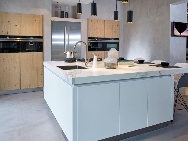 Deze Next125 by Tieleman keuken is prachtig. De witte keukenfrontjes combineren perfect met het aanrechtblad en het hout van de kasten waarin de inbouwapparatuur is ingebouwd. De koelkast is daarnaast ook zeer subtiel aanwezig in deze mooie keuken.