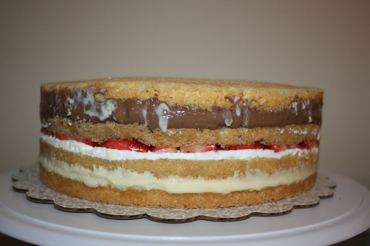 Italian rum/wedding/cream cake - a four layer italian sponge cake brushed with rum syrup then filled with vanilla and chocolate custard as well as whipped cream with fresh strawberries. i used a cake ring around the cake while assembling the layers.  that really helped ensure the fillings did leak out.  it set in the frig for an hour before i frosted.