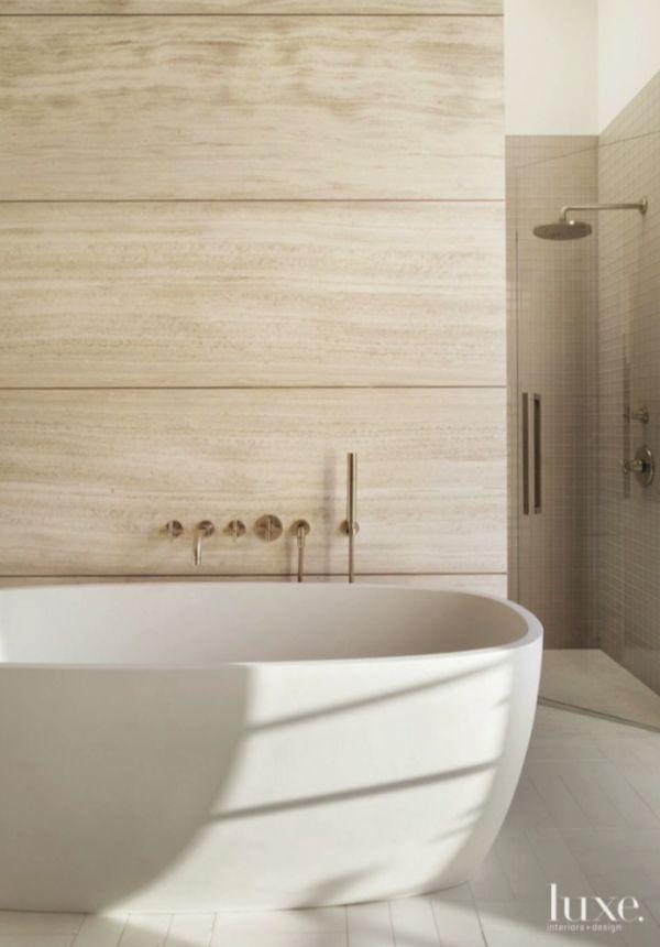 An agape soaking tub with dornbracht fittings backs up for Limestone tub