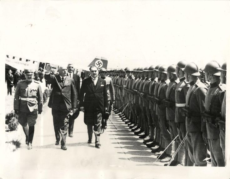 1937- Baron Von Neurath, German Foreign Minister, saluting Honor Guard, as he was greeted by Premier Stoyadinovitch (right) upon his arrival at Belgrade for conferences.