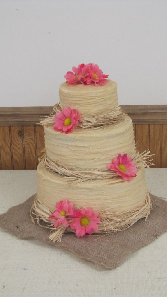 """You could wrap your wedding cake in hay and stick Dollar Tree daisies on it for that """"country"""" effect. But, WHY?"""