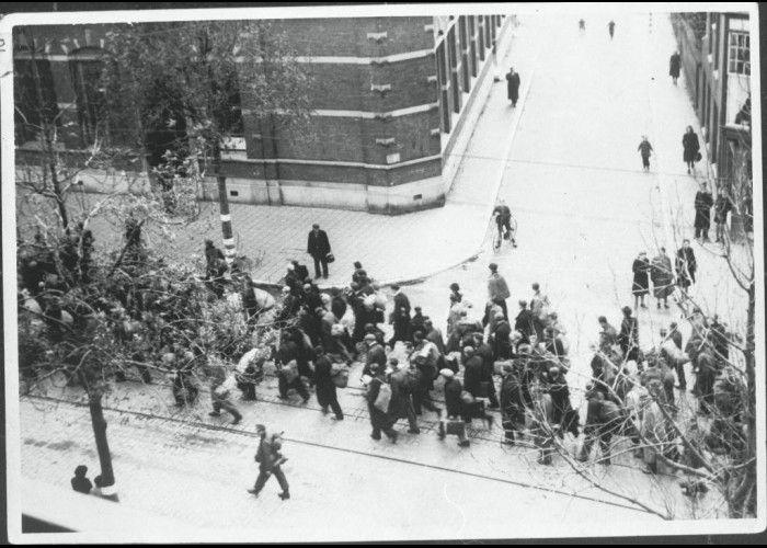 Rotterdamse mannen lopen over straat. Genomen vanuit een woning aan de Oudedijk in Rotterdam