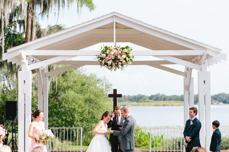 a sweet moment exchanging rings under the lakeside pavilion which was dressed overhead with a large arrangement of white, blush and pink roses, white stock, peach stock, white snapdragons, peach mini carnations, white mums, seeded eucalyptus and lemon leaf.