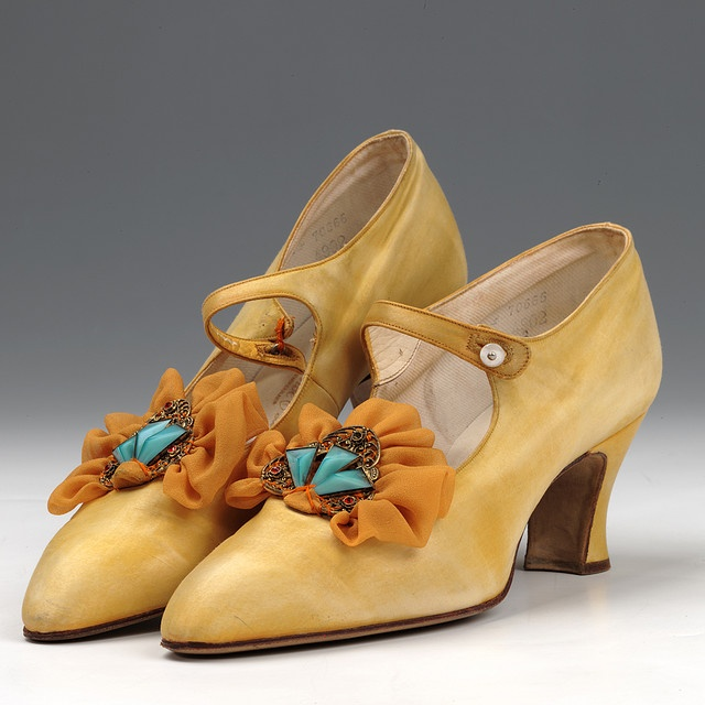 Yellow satin Mary Jane shoes, 1920s. Gilt brooch set with blue and red stones and crepe frill sewn on front (probably theatrical trimming added later). Northampton Museum & Art Gallery.