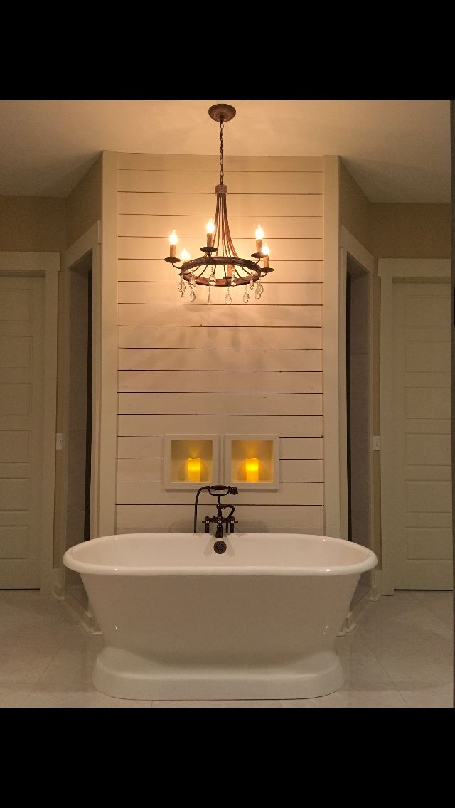 cast iron pedestal tub with shiplap accent wall in front of walk behind double shower